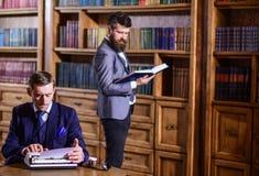 Escritor oldfashioned novo com a máquina de escrever na biblioteca com amigo farpado fotos de stock royalty free