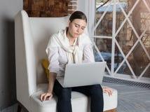 Escritor profissional fêmea cansado que lê seu artigo no rede-livro durante o dia longo do trabalho duro imagens de stock