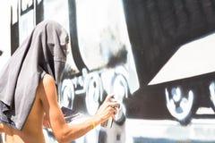 Escritor que trabaja en una pared de una manera anónima fotografía de archivo