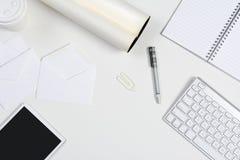 Escritorio blanco con la tableta y el teclado Foto de archivo