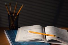 Escritorio con el libro de escuela en noche Foto de archivo libre de regalías