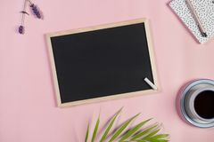 Escritorio con el tablero de tiza, la taza de café, la libreta y la pluma en un fondo rosa claro Visión superior fotografía de archivo libre de regalías