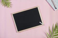 Escritorio con el tablero, la libreta y la pluma de tiza en un fondo rosa claro Visión superior fotos de archivo libres de regalías