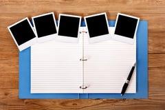 Escritorio con la carpeta azul del proyecto y las fotos en blanco Foto de archivo