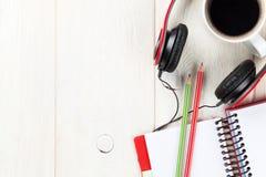 Escritorio con la libreta, el café y auriculares Imagen de archivo libre de regalías