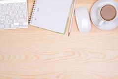 Escritorio con la libreta, el teclado, el ratón, el lápiz y una taza de café Fotos de archivo libres de regalías