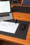 Escritorio con los documentos, el ordenador portátil y el smartphone Imagenes de archivo