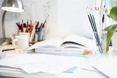 Escritorio con los libros; Papeles y cepillos fotos de archivo libres de regalías