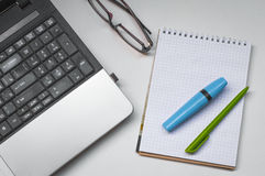 Escritorio con un ordenador portátil, un cuaderno y la pluma con un marcador Fotografía de archivo libre de regalías