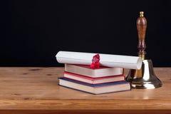 Escritorio de la escuela con el fondo del negro de la campana Imagen de archivo libre de regalías