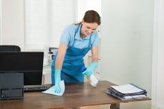 Escritorio de la limpieza del trabajador con el trapo