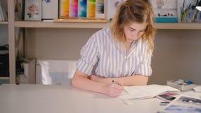 Escritorio de la mujer del artista que bosqueja el estudio casero del arte almacen de metraje de vídeo
