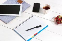Escritorio de la tabla de la oficina con el sistema de fuentes, libreta en blanco blanca, taza, pluma, tableta en el fondo blanco Fotos de archivo