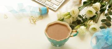 Escritorio de la tabla de la oficina con el ordenador, las flores blancas del ramo hermoso, la taza de cacao y el regalo Foto de archivo