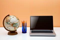 Escritorio de los estudiantes con el globo, los lápices y la computadora portátil Fotos de archivo