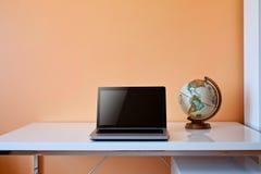 Escritorio de los estudiantes con el globo y la computadora portátil Imagenes de archivo