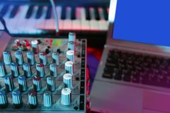 Escritorio de música audio del mezclador bajo luces coloridas Foto de archivo