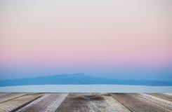Escritorio de madera con el espacio libre y el fondo borroso del paisaje en la puesta del sol Imagen de archivo libre de regalías
