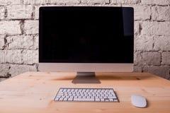 Escritorio de madera con el ordenador, el teclado y el ratón Pared de ladrillo imagenes de archivo