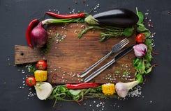 Escritorio de madera con la frontera de las verduras en fondo oscuro Imagen de archivo
