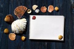 Escritorio de madera con las cáscaras del mar y la libreta blanca Fotos de archivo