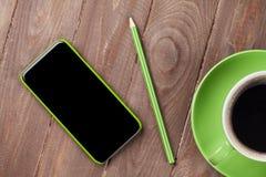 Escritorio de madera de la oficina con smartphone y café Imagenes de archivo