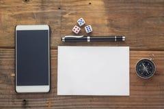 Escritorio de madera del fondo con el papel, los dados, el compás, el teléfono elegante y la pluma imagenes de archivo