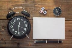 Escritorio de madera del fondo con el reloj, el papel, los dados, el compás y la pluma fotos de archivo