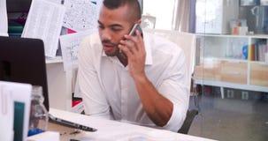 Escritorio de In Office At del hombre de negocios que habla en el teléfono móvil almacen de metraje de vídeo