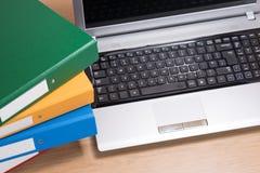 Escritorio de oficina aseado con el ordenador portátil y las carpetas apiladas Fotos de archivo