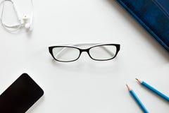 Escritorio de oficina blanco con los vidrios, los lápices, los auriculares y el móvil Imagen de archivo