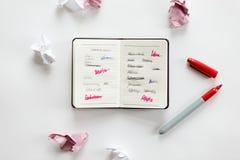Escritorio de oficina blanco con un cuaderno abierto y un papel arrugado Imagen de archivo libre de regalías