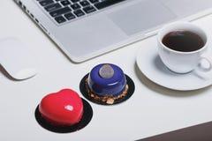 Escritorio de oficina con el ordenador portátil de las galletas del café fotografía de archivo