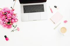 Escritorio de oficina con el ordenador portátil, ramo rosado de las rosas, taza de café, diario rosado en el fondo blanco Endecha fotografía de archivo
