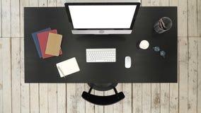 Escritorio de oficina con el ordenador y la pantalla vistos a la cámara Visualización blanca almacen de video