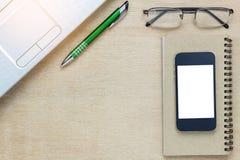 Escritorio de oficina de los accesorios el teléfono móvil, papel de nota, revestimiento Foto de archivo libre de regalías