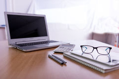Escritorio de oficina de madera con el ordenador portátil, plumas, vidrios imagenes de archivo