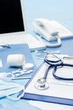 Escritorio de oficina del doctor con los accesorios médicos Imagenes de archivo