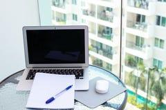 Escritorio de oficina del trabajo con un ordenador portátil del ordenador, cuaderno, pluma en la tabla de cristal foto de archivo