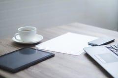 Escritorio de oficina en blanco con compu del ordenador portátil del smartphone de la tableta de la taza de café Imagen de archivo libre de regalías