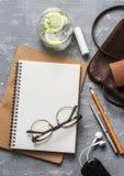Escritorio de oficina femenino de la endecha plana con la libreta, la tableta, el bolso de cuero, los vidrios, los auriculares, e imagen de archivo