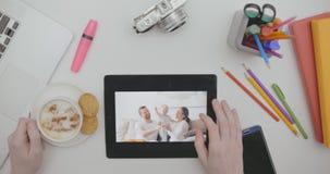 Escritorio de oficina de la visión superior con la tableta con las fotos de familia en la pantalla y la mano masculina almacen de metraje de vídeo