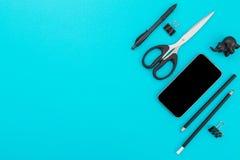 Escritorio de oficina plano de la endecha Espacio de trabajo con los accesorios masculinos: teléfono móvil, lápiz, pluma, tijeras Fotos de archivo