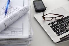 Escritorio de oficina que una pila de informes del papel de ordenador trabaja Fotos de archivo