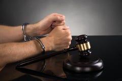 Escritorio de Person Hand In Handcuffs At Fotos de archivo libres de regalías