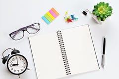 Escritorio de trabajo con el cuaderno, las lentes y el despertador abiertos Imagenes de archivo