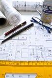 Escritorio del arquitecto con los rodillos y los planes imagenes de archivo