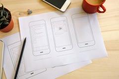 Escritorio del diseñador con bosquejos del wireframe de UI Fotografía de archivo libre de regalías