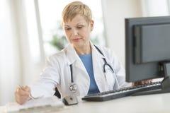 Escritorio del doctor Working At Computer en clínica Imágenes de archivo libres de regalías