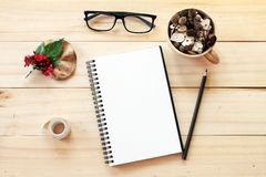 Escritorio del espacio de trabajo con el cuaderno, el lápiz, los conos del pino en taza de madera del té, los vidrios del ojo, la Foto de archivo